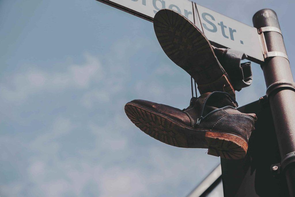Shoe hanging on street sign